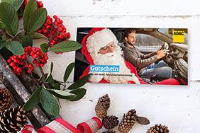 Bild eines ADAC-Gutscheins umgeben von weihnachtlicher Dekoration.