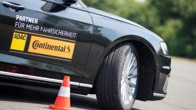 Aufnahme der Beifahreraussenseite eines schwarzen Autos mit den Logos des ADAC und Continental darauf.