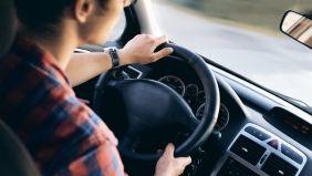 Aufnahme eines jungen Fahrers in einem Auto sitzend mit den Händen am Steuer.