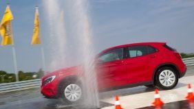 Ein rotes Auto fährt einen Parcours mit Hütchen und Wasserfontaine.