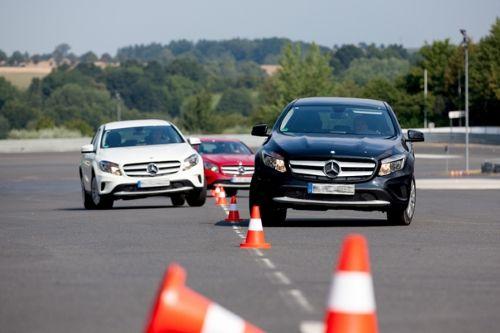 Drei Autos fahren hintereinander einen Parcour auf einer Straße mit Hütchen entlang.