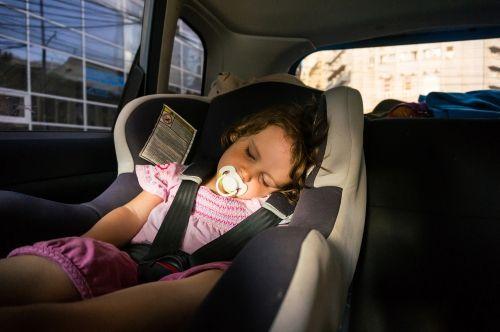 Ein Kleinkind sitzt in einem Kindersitz auf der Rückbank und schläft.