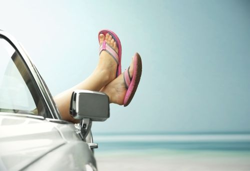 Füße mit Flip Flops bekleidet welche aus dem Beifahrerfenster gehalten werden.