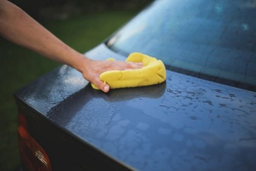 Der Kofferraum eines Autos wird von außen mit einem Schwamm geputzt.