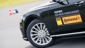 Detailaufnahme des Vorderteils eines Autos mit den Logos von ADAC und Continental auf der Fahrertür.