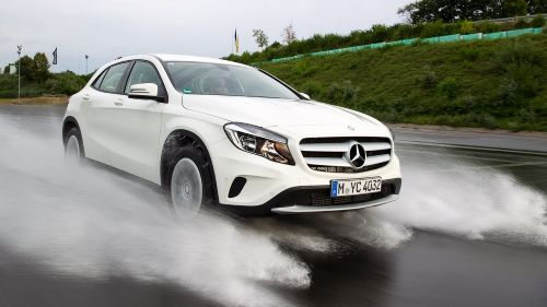 Ein weißer Mercedes fährt auf einer nassen Fahrbahn.