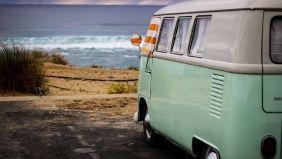 Hellgrüner Vintage-Van steht auf einem Parkplatz mit Strand und Meer im Hintergrund.