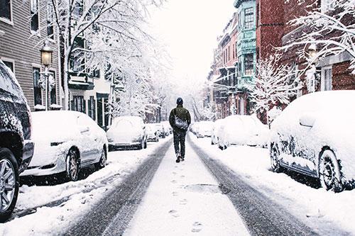 Eine Person läuft durch eine verschneite Straße, an der Autos parken.